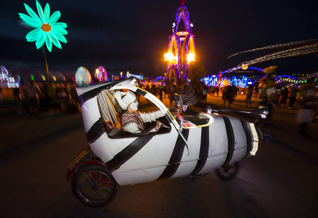 A costumed performer drives around the speedway during the second day of the Electric Daisy Car ...