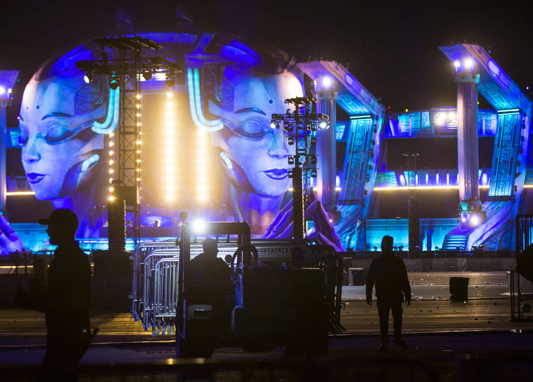 Event officials clear the area at the Kinetic Field stage after it was shut down due to high wi ...