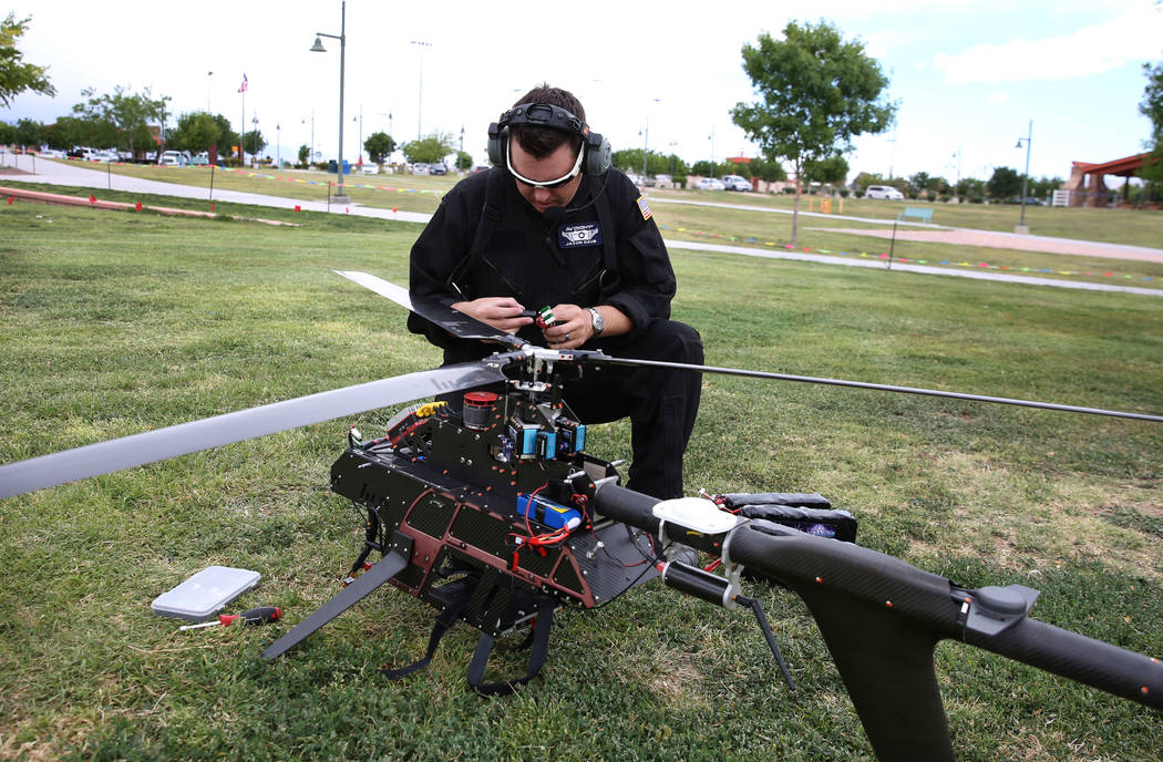 Jason Daub, a pilot in command, inspects before flying the Vapor 55 unmanned helicopter over Cr ...