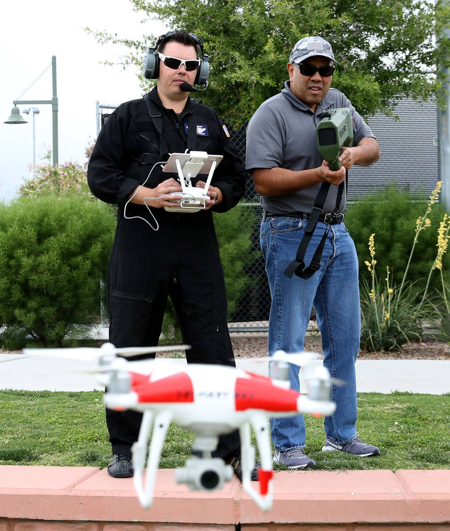 Jason Daub, a pilot in command, left, flies his Phantom IV drone as Andy Morale, director of bu ...