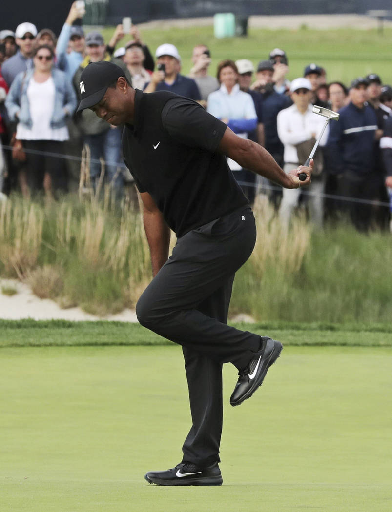 Tiger Woods reacts after missing a putt for birdie on the 17th green during the second round of ...