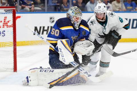 St. Louis Blues goaltender Jordan Binnington (50) protects the puck as San Jose Sharks center M ...