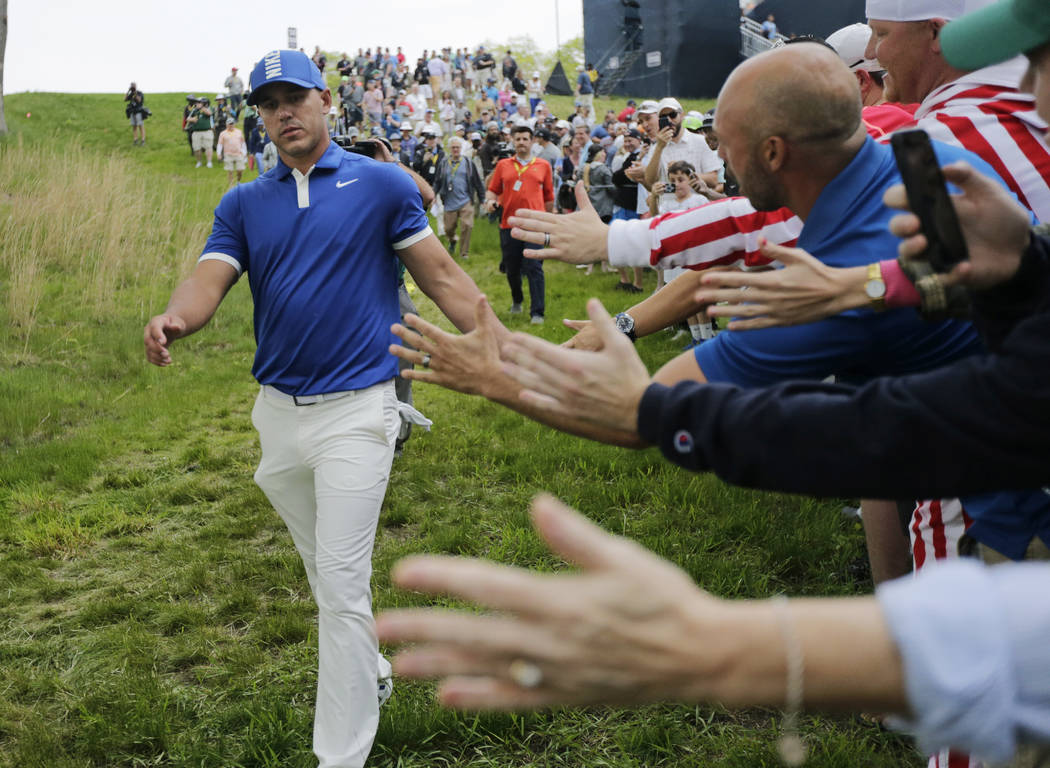Brooks Koepka greets spectators as he walks down to the 15th tee during the second round of the ...