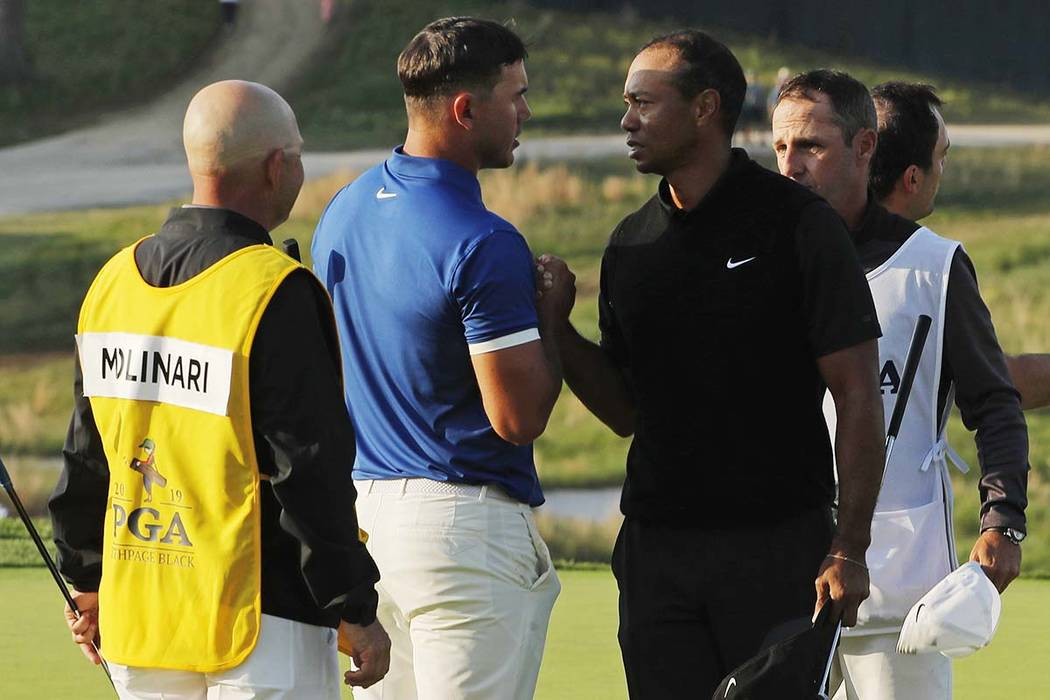 Brooks Koepka and Tiger Woods shake hands after finishing the second round of the PGA Champions ...