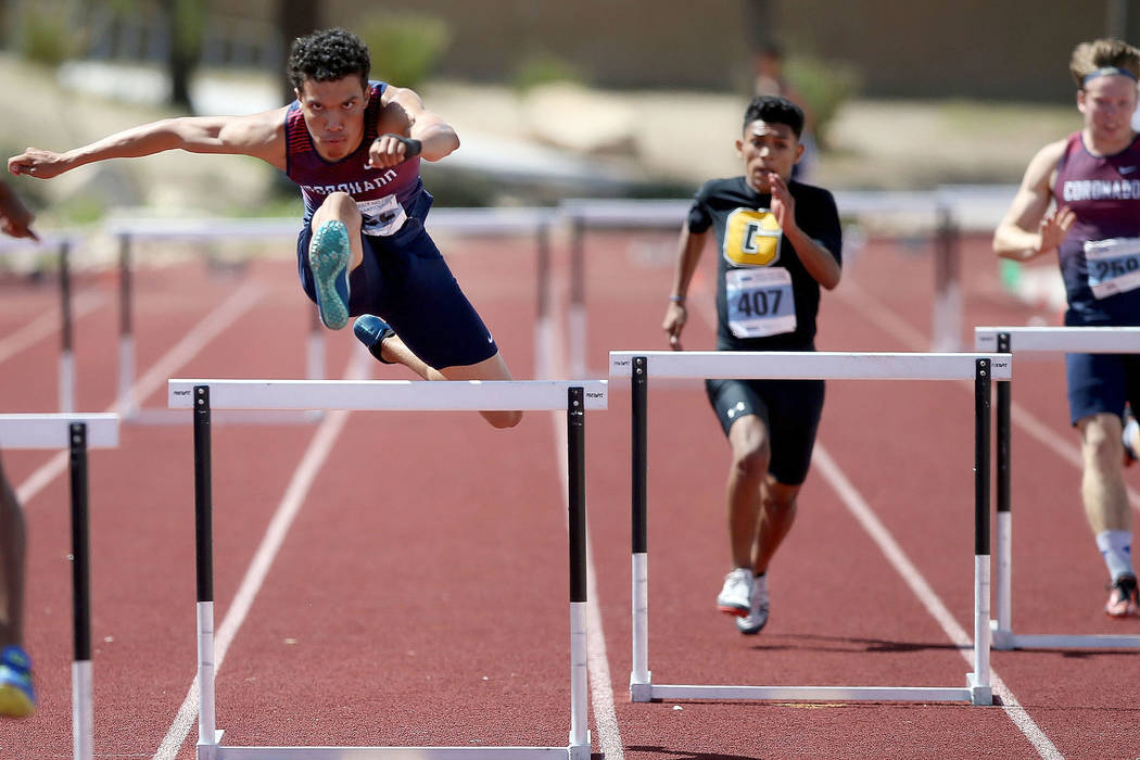 Justin Watterson of Coronado, left, on his way to winning Class 4A 300 meter hurdles in the sta ...