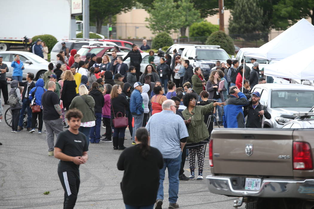 Students gather outside Parkrose High School during a lockdown after a man armed with a gun wa ...
