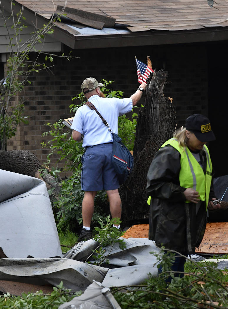 Letter carrier James Hurtado resets a small U.S. flag into a tree stump while delivering the ma ...