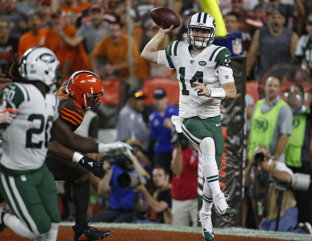 New York Jets quarterback Sam Darnold, right, throws a pass against the Cleveland Browns during ...