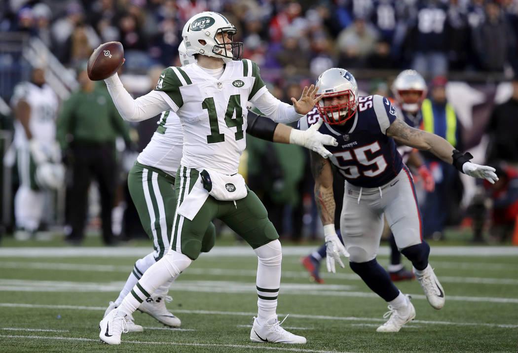 New York Jets quarterback Sam Darnold, left, passes under pressure from New England Patriots de ...