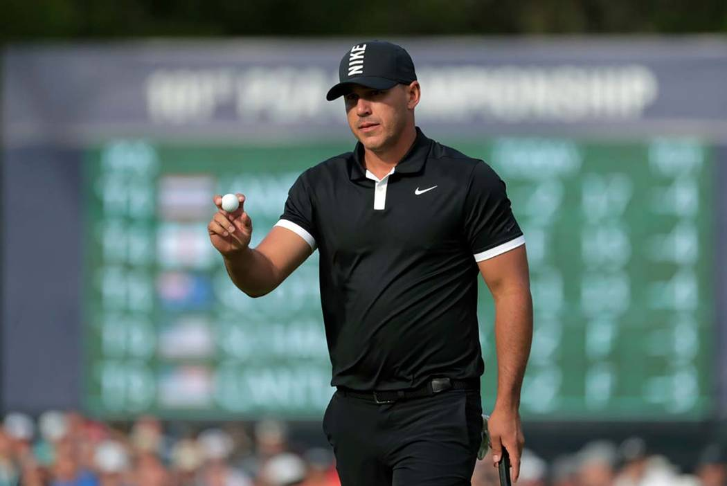 Brooks Koepka reacts after putting on the 13th green during the third round of the PGA Champion ...