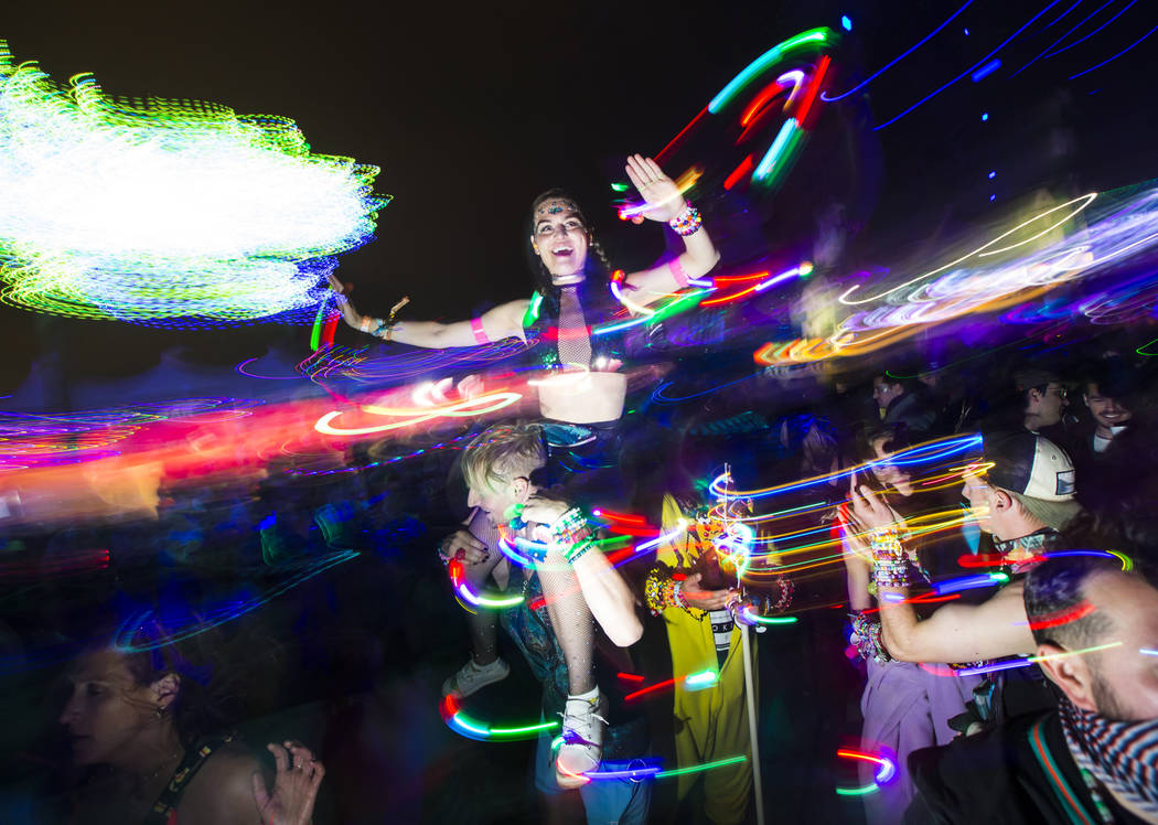 Attendees dance as Skrillex, not pictured, performs at the Circuit Grounds stage during the sec ...