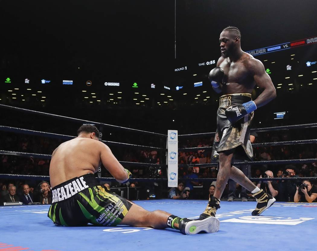 Deontay Wilder, right, knocks down Dominic Breazeale during the first round of a WBC heavyweigh ...