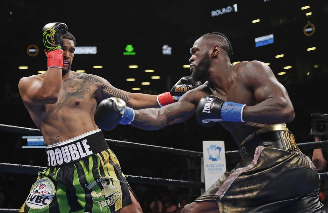 Dominic Breazeale, left, evades a right from Deontay Wilder during the first round of the WBC h ...