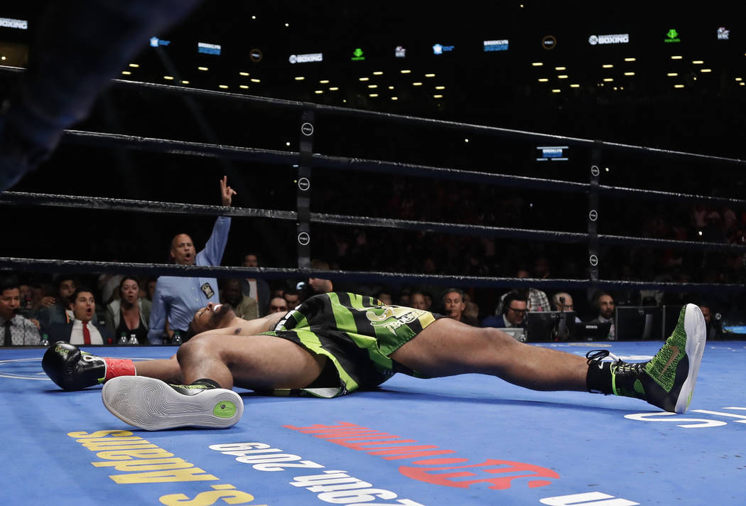 Dominic Breazeale lies on the mat after being knocked down by Deontay Wilder during the WBC hea ...
