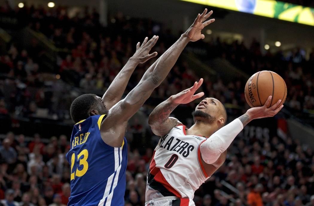 Portland Trail Blazers guard Damian Lillard, right, shoots over Golden State Warriors forward D ...