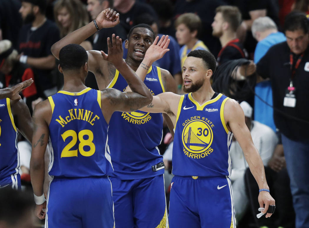 Golden State Warriors guard Stephen Curry, right, greets Alfonzo McKinnie (28) and Kevon Looney ...