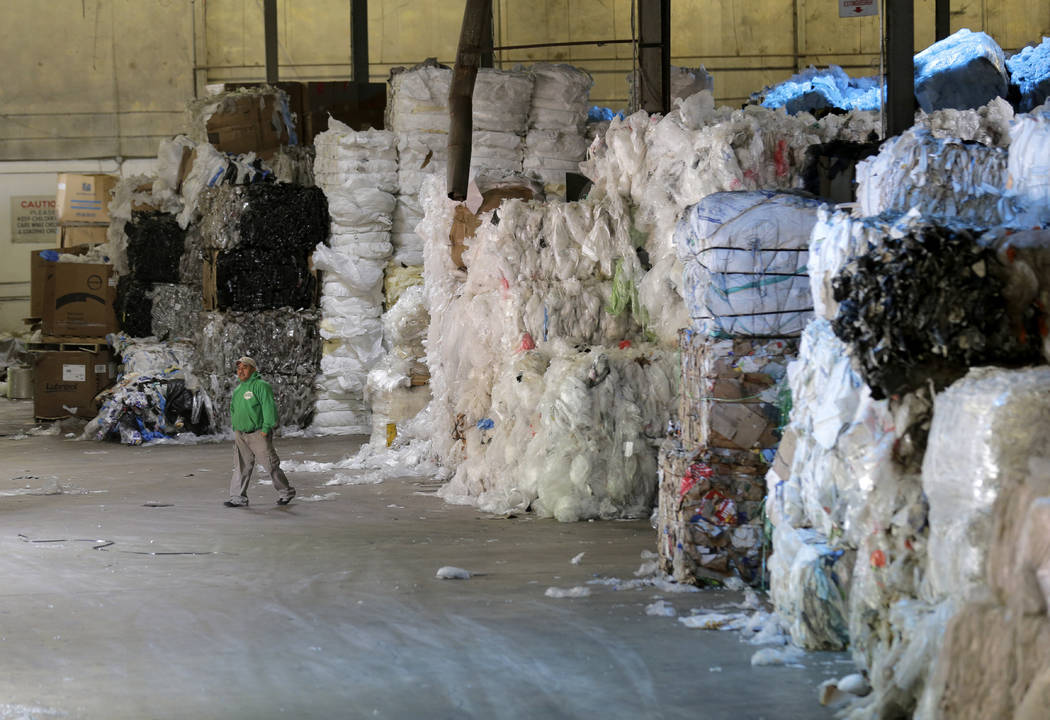 In this May 7, 2019 photo, a man walks under towers of recyclables at a GDB International wareh ...