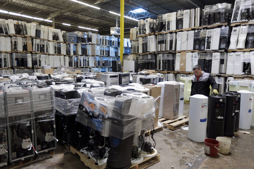 In this May 7, 2019 photo, water coolers are stacked and ready to be broken down into parts for ...