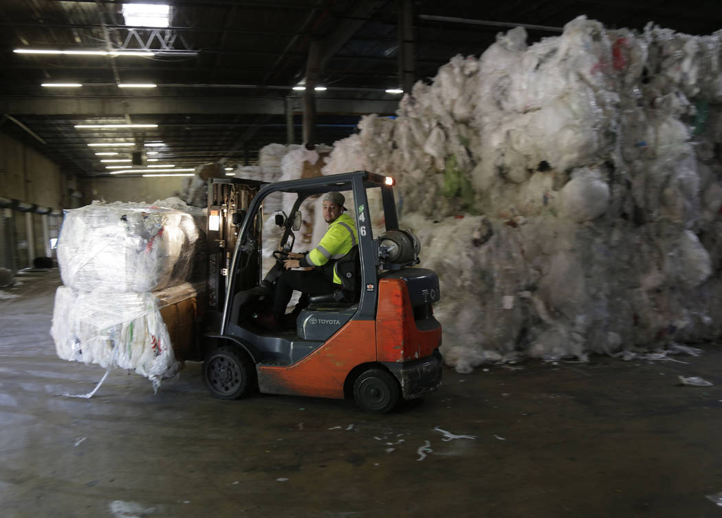 In this May 7, 2019 photo, a forklift moves through stacks of recyclables at a GDB Internationa ...