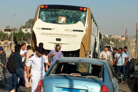 Police inspect a car and a bus that were damaged by a bomb, in Cairo, Egypt, Sunday, March 19, ...