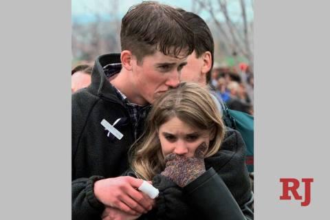 FILE - In this April 25, 1999 file photo, shooting victim Austin Eubanks hugs his girlfriend du ...