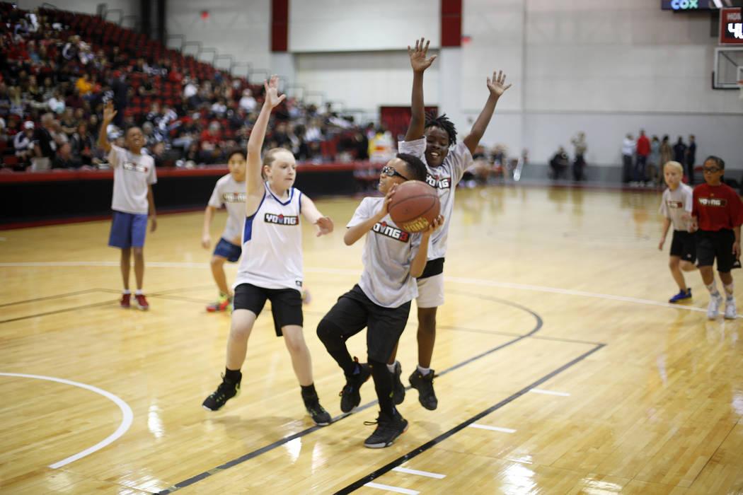 Kaelie Pernyall, 12, left, attempts to block Jackson Livingston, 10, alongside Micah Uthman, 10 ...