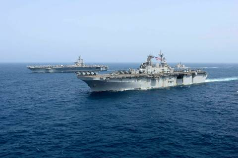 The amphibious assault ship USS Kearsarge sails Friday, May 17, 2019, in front of the USS Abrah ...