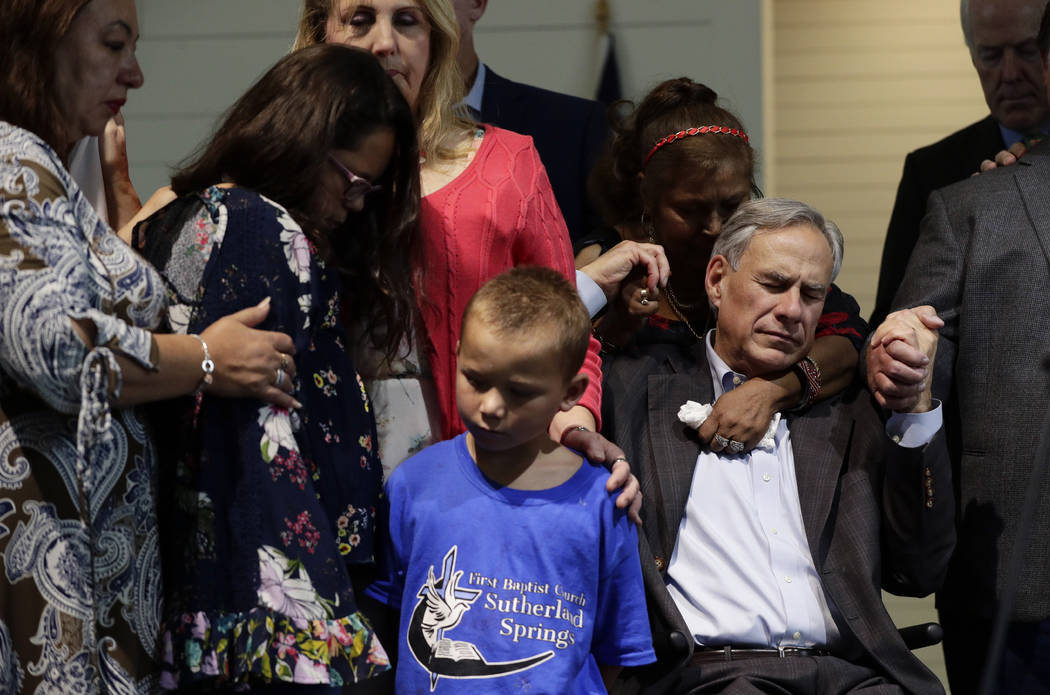 Texas Gov. Greg Abbott, right, holds hands with survivors during a dedication ceremony for a ne ...