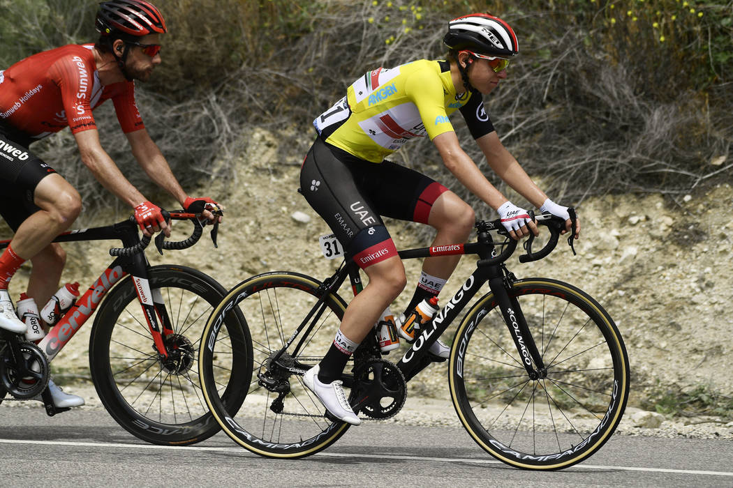 Tadej Pogacar, right, of Slovenia, rides along with the peloton during the seventh and final st ...