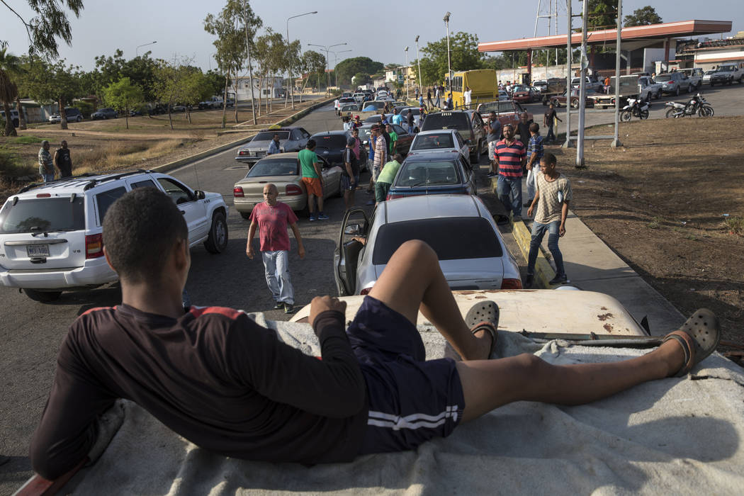 People line the street with their vehicles as they wait to fill up with gas at a fuel station, ...