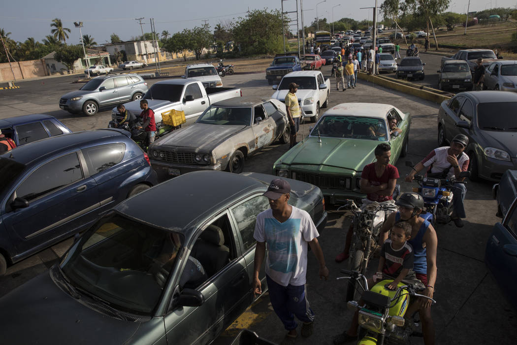 A line of cars spills on to the street as drivers wait to fill their tanks at a fuel station in ...