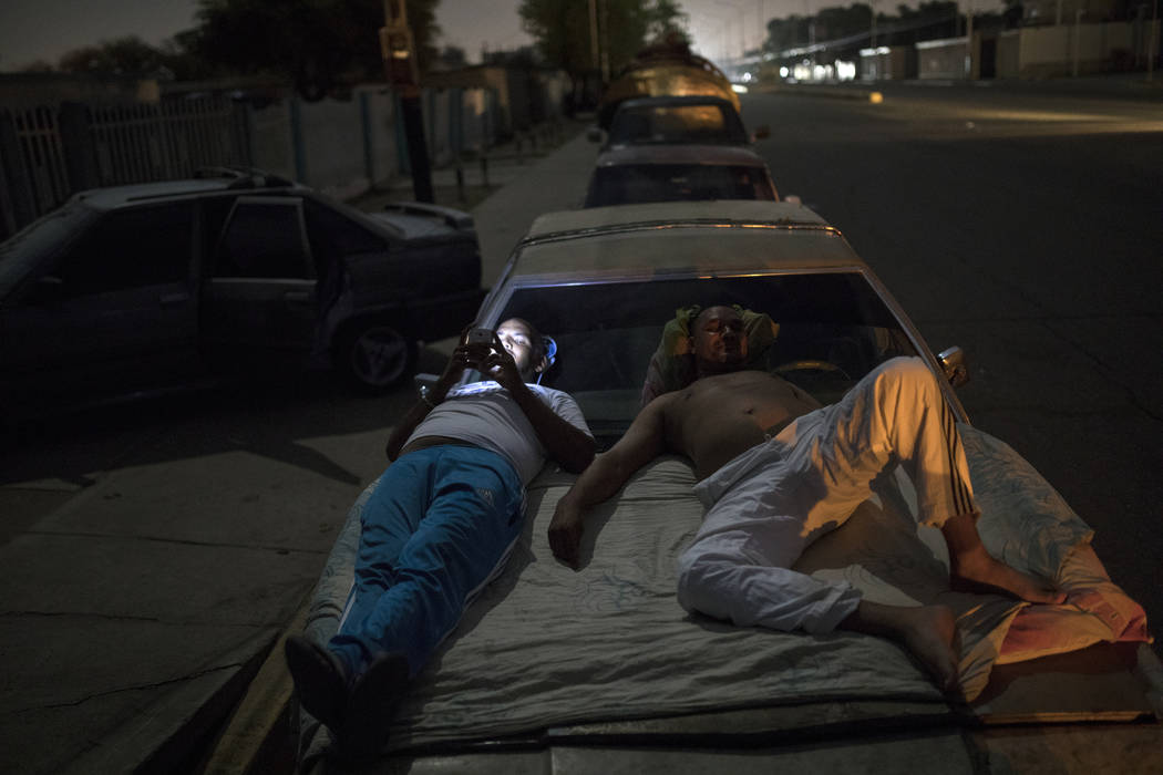 Andres Quintero, left, and Fermin Perez rest on top of Perez's car as they wait in line for ove ...