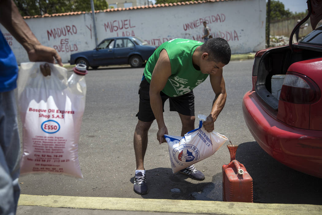 Jesus Gonzales fills a container with bagged gasoline he bought at extra cost at a fuel station ...