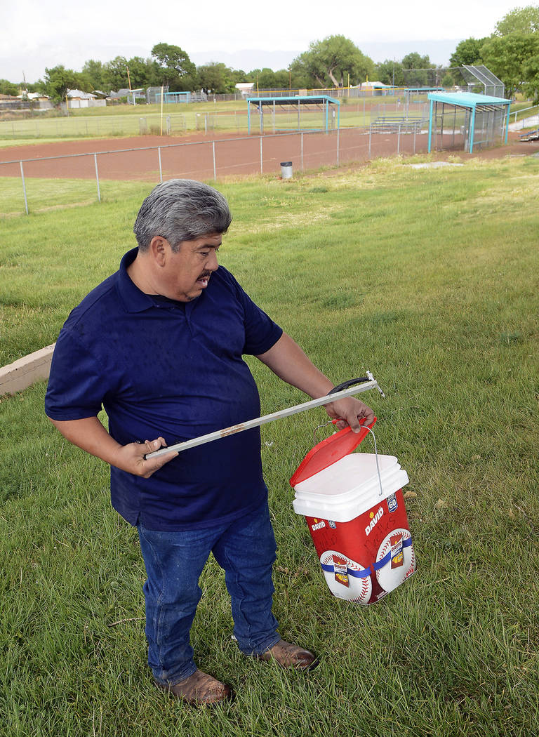 Hector Aguilar uses a claw grabber extension to remove a hypodermic needle from one of the base ...