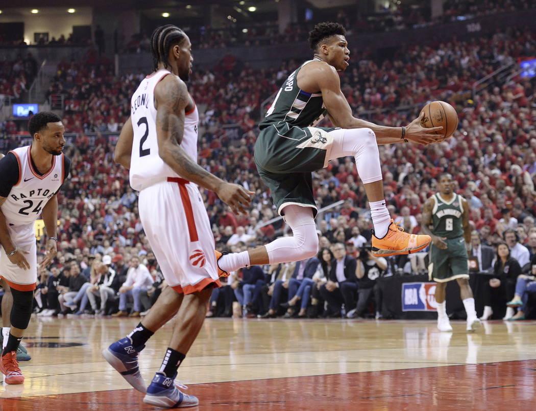 Milwaukee Bucks forward Giannis Antetokounmpo (34) drives to the net past Toronto Raptors forwa ...