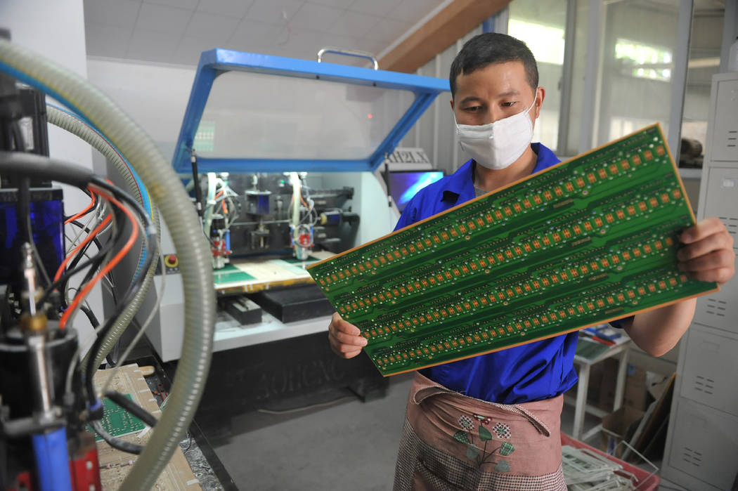 A staff member works in a circuit board manufacturing facility May 22, 2018, in Hangzhou in eas ...