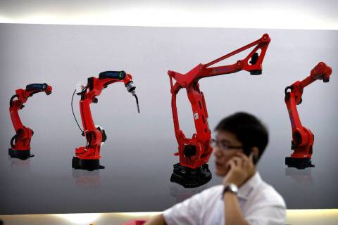 A visitor talks on his smartphone in front of a display of manufacturing robots from a Chinese ...