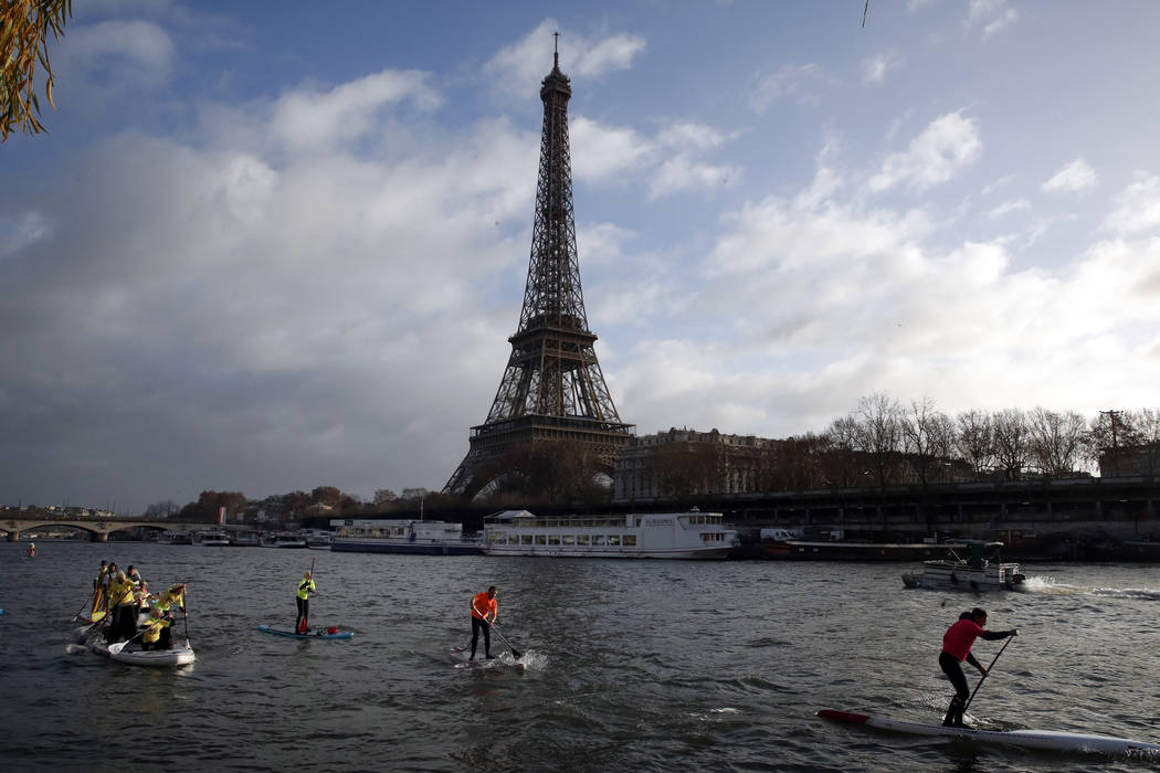 In this Dec.9, 2018 file photo, competitors paddle on the Seine river in front of the Eiffel To ...