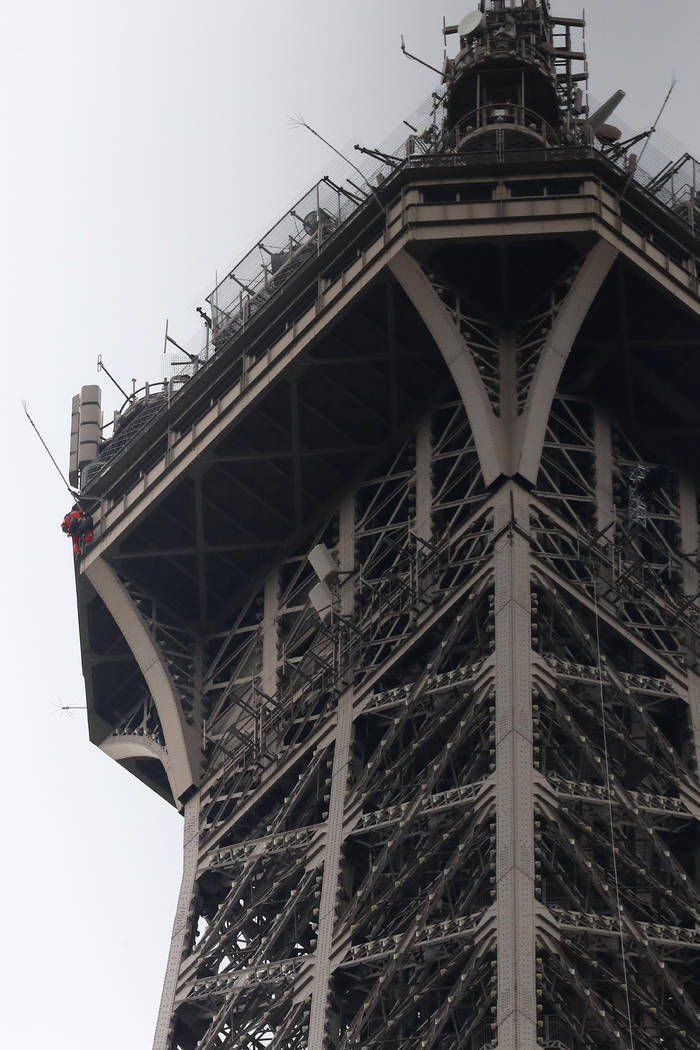 A rescue worker, left in red, climbs the Eiffel Tower Monday, May 20, 2019 in Paris. The Eiffel ...