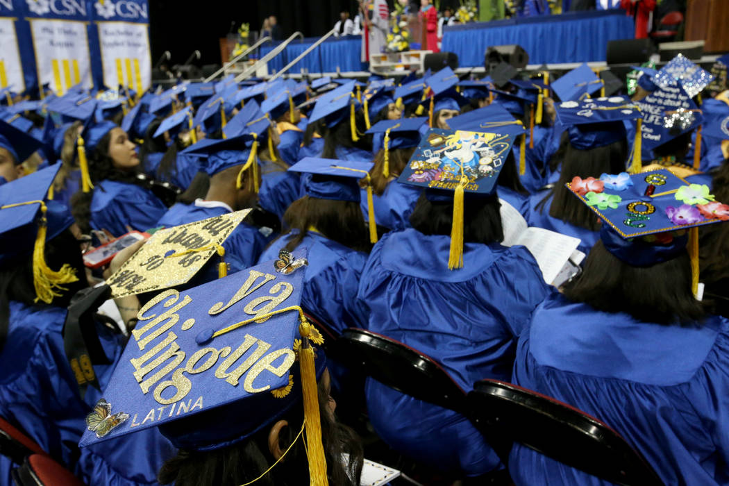 Graduates, including Rosario Hernandez, left, don personalized mortarboards during College of S ...