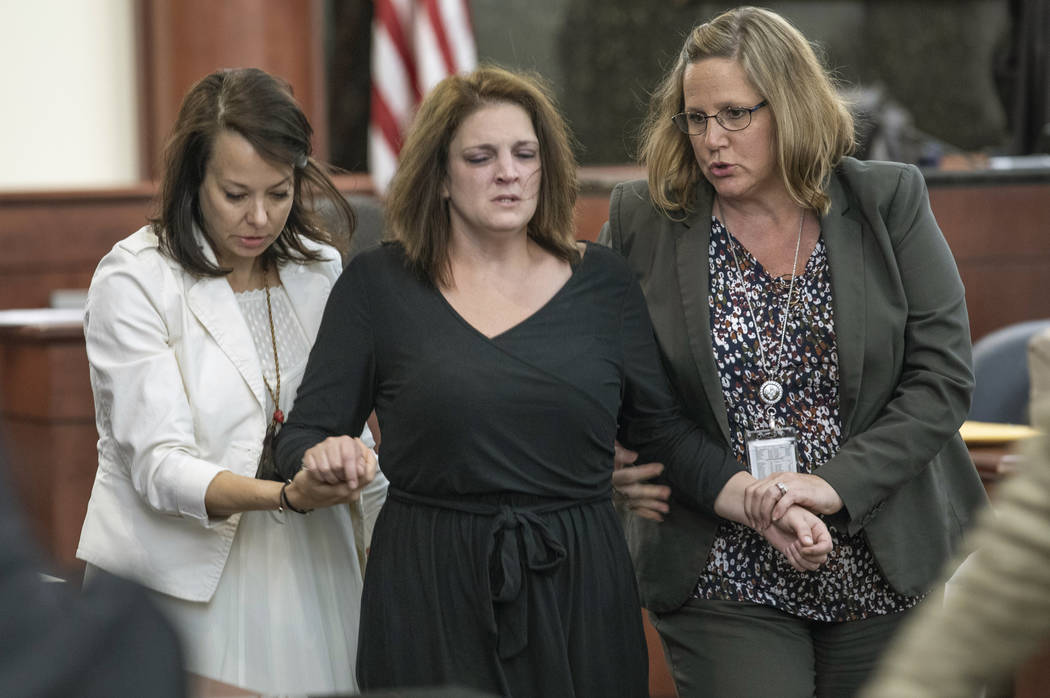 Amber Kyzer is helped out of the courtroom after breaking down on the witness stand while being ...