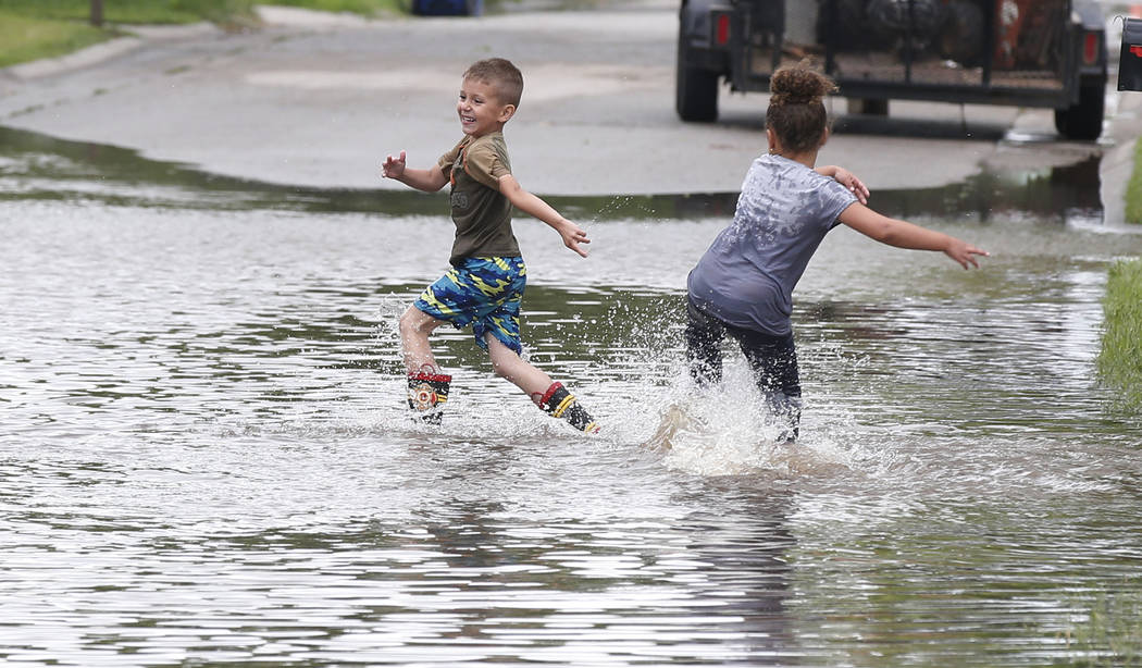 Kayden Evans, left, 6, and Keely Younger, 6, play in the water on a flooded street in El Reno, ...