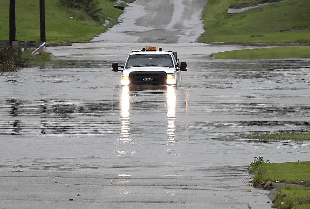 A pickup truck drives on a flooded street in Enid, Okla., Monday, May 20, 2019. An intense stor ...