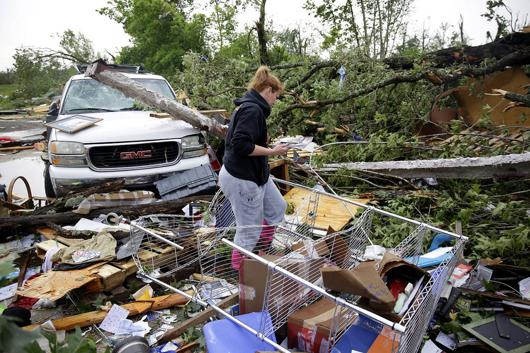 Michelle Underwood searches through the wreckage of a feed store where she stored most of her b ...