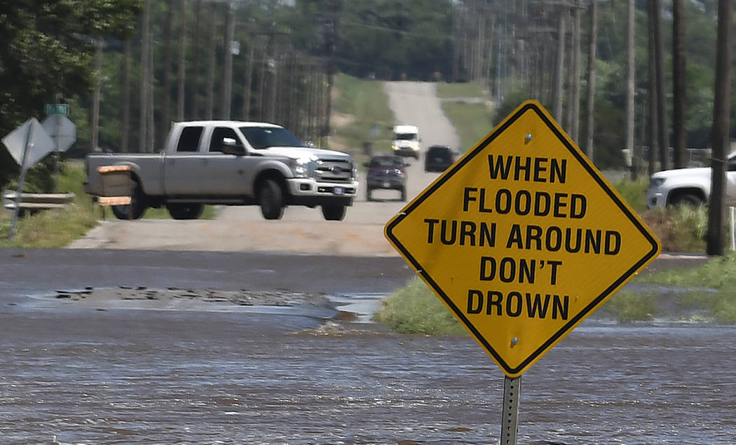 Traffic turns around as flood water covers 13th street in Kingfisher, Okla., Tuesday, May 21, 2 ...