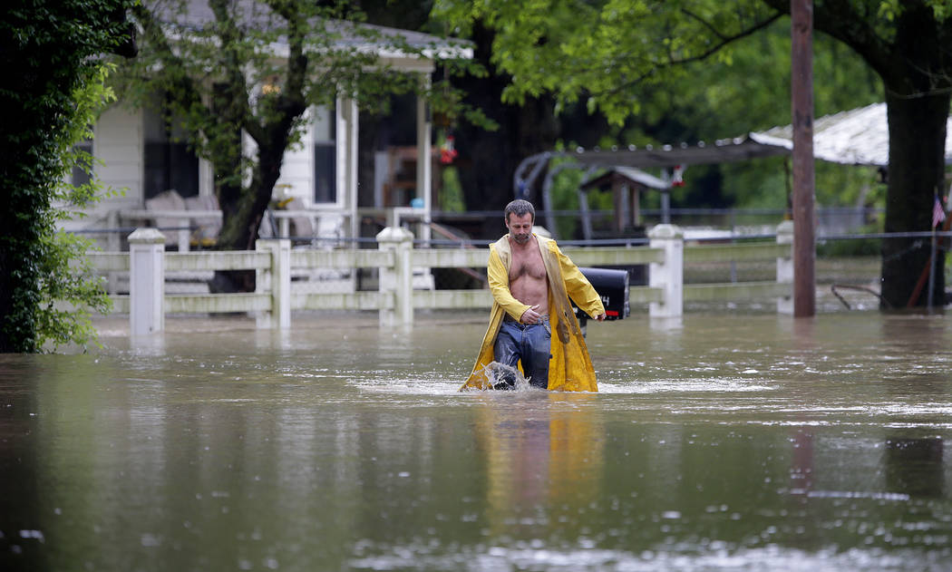 David Dick wades out of the water after checking on his flooded home in Sperry, Okla., Tuesday, ...