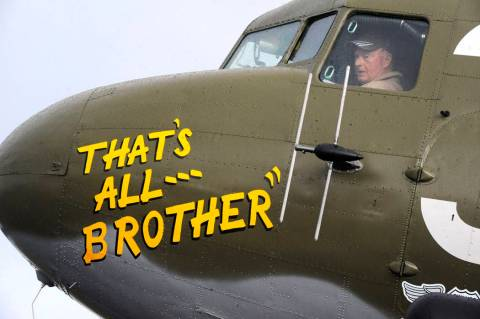 Pilot Tom Travis sits in the cockpit of the World War II troop carrier That's All, Brother duri ...