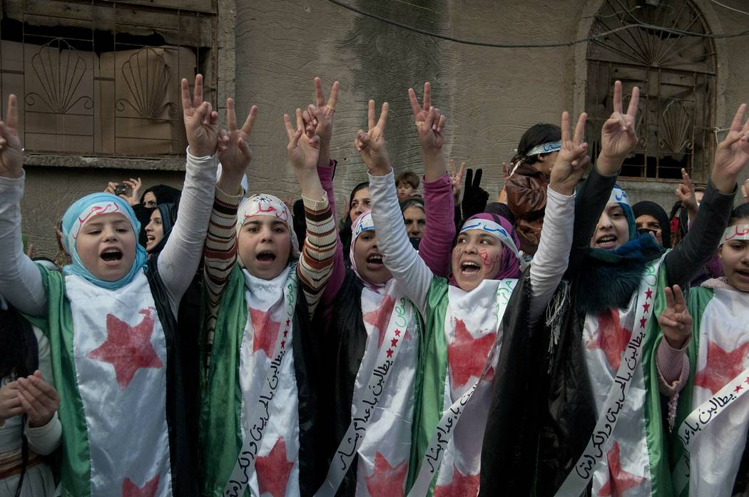 Anti-Syrian regime protesters flash the victory sign Dec. 21, 2011, as they wear Syrian revolut ...