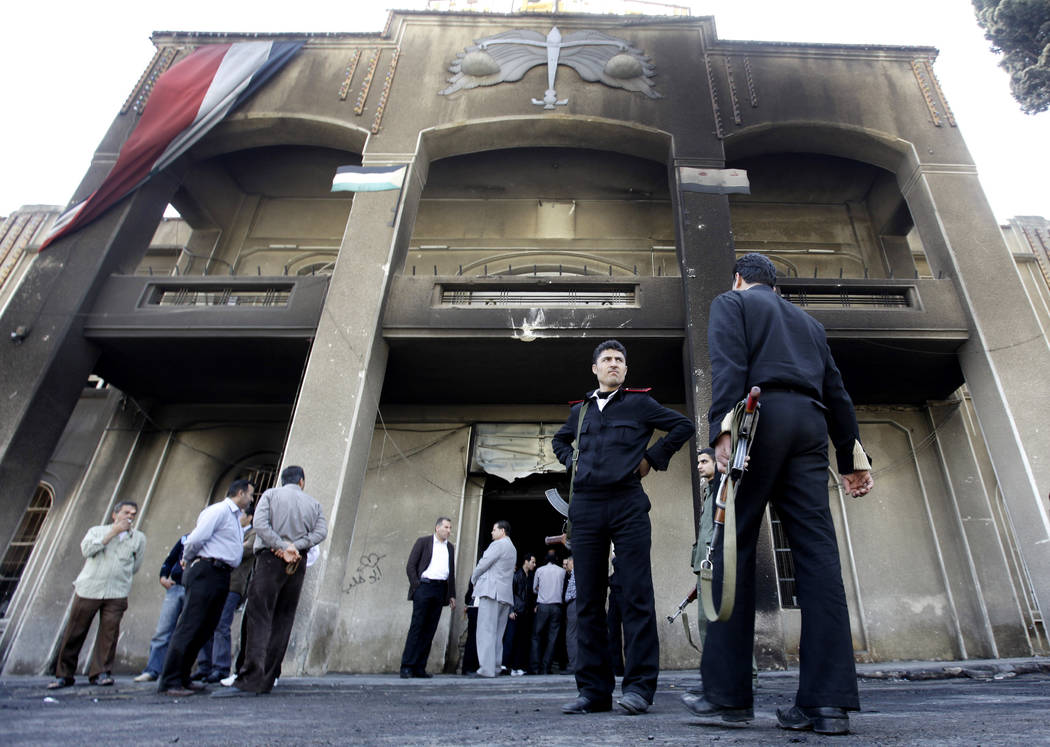 FILE - In this March 21, 2011 file photo, Syrian policemen stand in front of a court building t ...