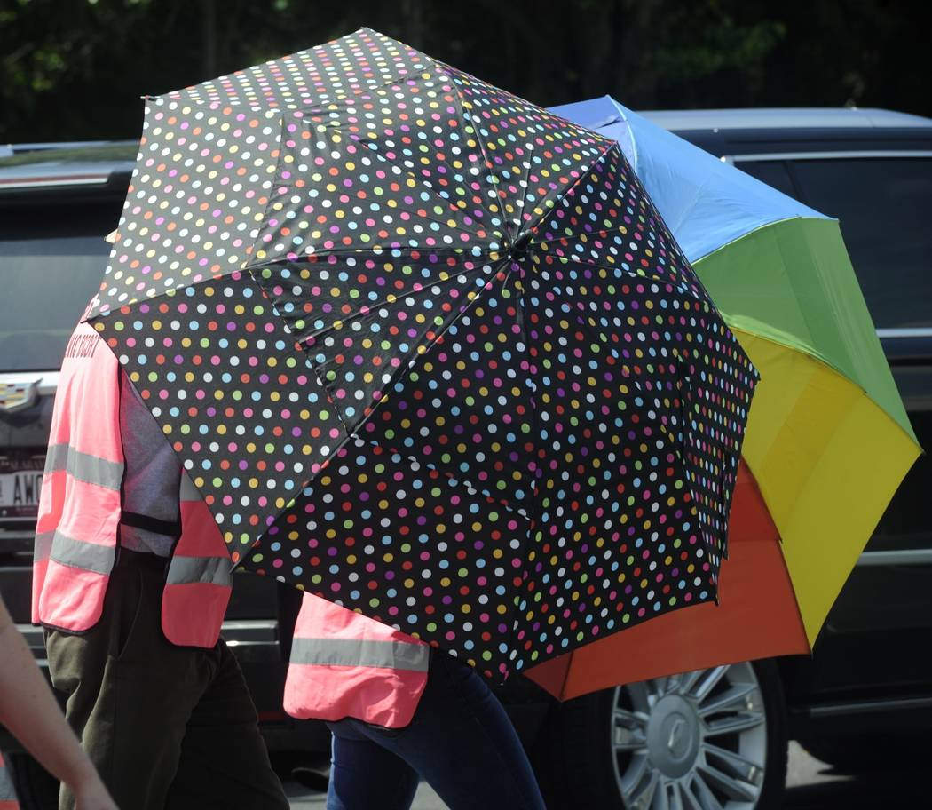 Escorts, using umbrellas, shield clients from the gestures and voices of anti-abortion activist ...